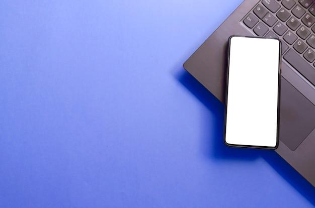 Komputer laptop smartfon na białym tle ekran na niebieskim tle obszaru roboczego