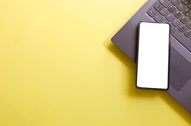 Komputer laptop smartfon na białym tle ekran na żółtym tle obszaru roboczego