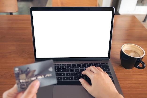 Komputer laptop z pusty biały ekran i karta kredytowa na drewnianym stole w kawiarni