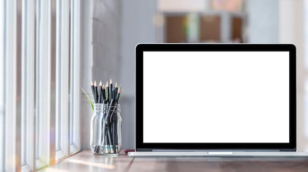 Komputer laptop z pustym ekranem na stole we współczesnym pokoju. makieta laptopa z pustym ekranem do projektowania graficznego.