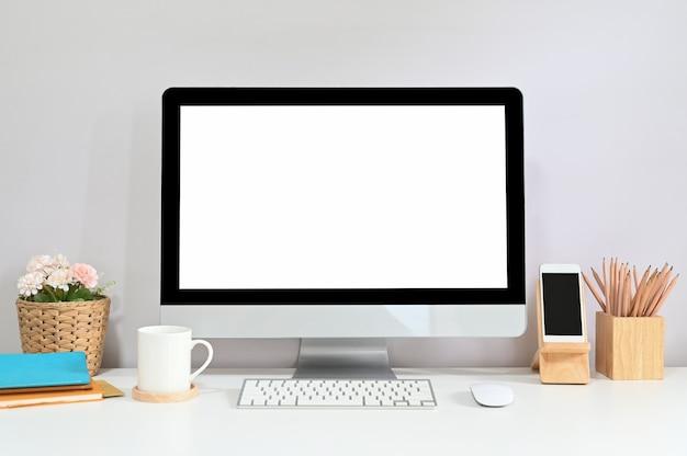 Komputer obszaru roboczego z białym pustym ekranem kładzie się na biurku w otoczeniu różnych urządzeń.