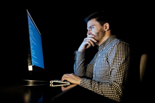 Komputer programisty w ciemnym domowym biurze