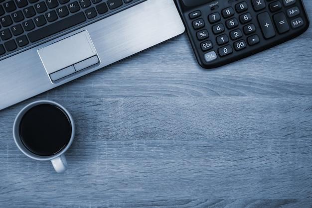 Komputer przenośny lub notebook, kalkulator i filiżanka kawy