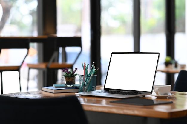 Komputer przenośny z pustym ekranem, reklama filiżanki kawy materiały biurowe na drewnianym biurku