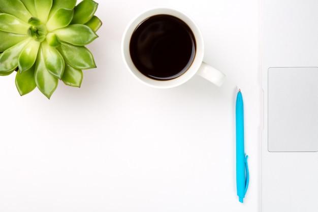 Komputer przenośny z rośliną w doniczce, filiżanką kawy i niebieskim piórem na białej powierzchni.