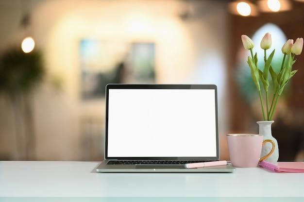 Komputer przenośny z słoikiem tulipanów i filiżanką kawy