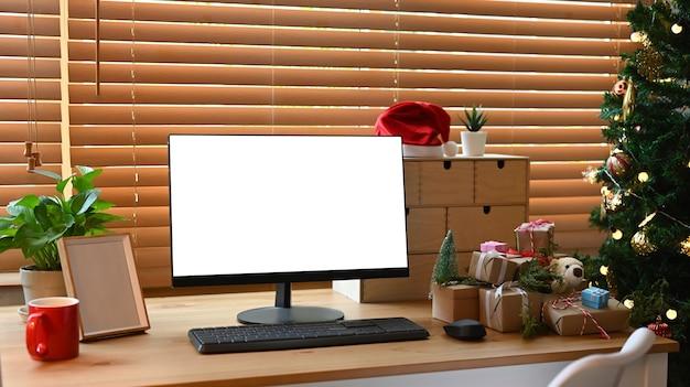 Komputer, pudełka na prezenty i filiżanka kawy na drewnianym stole w pobliżu choinki w salonie.