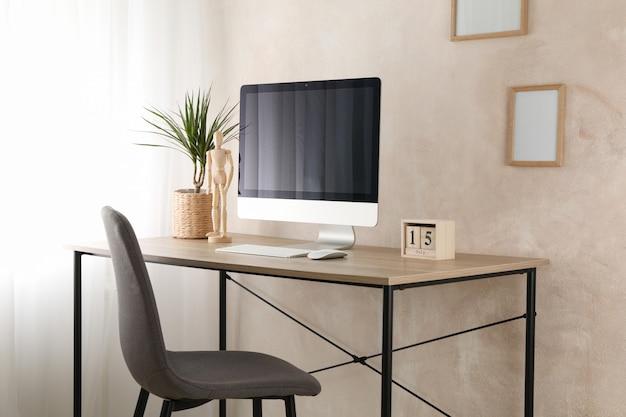 Komputer, roślina i drewniany mężczyzna na drewnianym stole. pokój do pracy