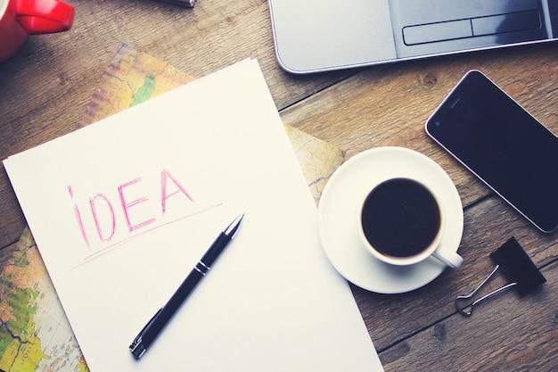 Komputer, smartfon, filiżanka kawy, papier i długopis na drewnianym stole
