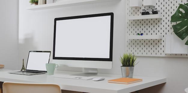 Komputer stacjonarny i laptop z pustym ekranem z kopią i dekoracjami biurowymi w minimalnym białym pokoju biurowym