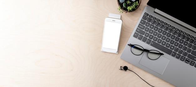 Komputer, telefon z makietą, mikrofon ue drewniany stół z miejscem na kopię. koncepcja edukacji online, koncepcja biznesowa.