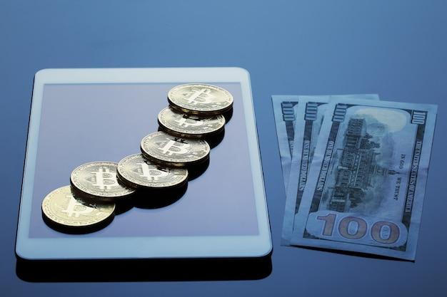 Komputer typu tablet, bitcoiny i sto banknotów dolarowych