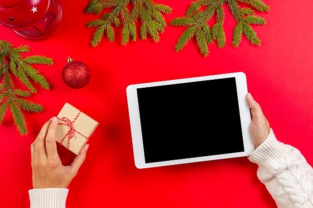 Komputer typu tablet w ręce kobiety na czerwono z dekoracji świątecznych