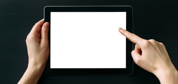Komputer typu tablet z białym pustym ekranem w rękach na białym na czarnym tle.
