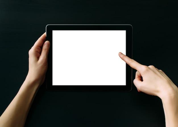 Komputer typu tablet z białym pustym ekranem w rękach na czarnym stole. trzymając i wskazując na pusty ekran na cyfrowym tablecie. skopiuj miejsce.