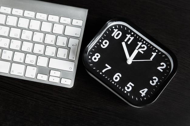 Komputer z białą klawiaturą i czerń zegarem na drewnianym stole. szablon