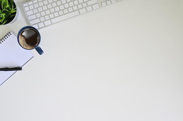 Komputerowa klawiatura z kawą, notatnikiem i piórem na biurowym pulpitu widoku strzale.