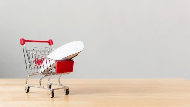 Komputerowa mysz na wózek na zakupy na drewno stole.