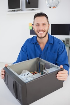 Komputerowego inżyniera obsiadanie z otwartym komputerem ono uśmiecha się przy kamerą w jego biurze