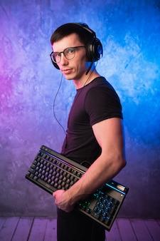 Komputerowy frajer z klawiaturą nad kolorową różową i niebieską neonową ścianą