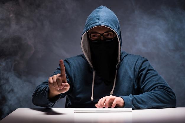 Komputerowy hacker pracuje w ciemnym pokoju
