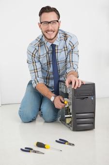 Komputerowy inżynier pracuje na łamanej konsoli z śrubokrętem