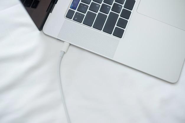 Komputerowy laptop ładuje baterię na łóżku w sypialni w domu. technologia, wiele opcji ładowania i koncepcje stylu życia
