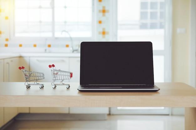 Komputerowy laptop, notatnik lub dwa mini wózek na zakupy na stole w kuchennym pokoju w domu.