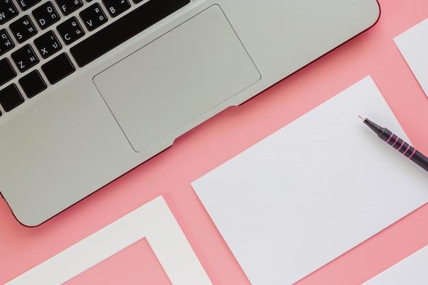 Komputerowy laptop z białą ramą, papierowymi kartami i piórem na różowym koloru tle