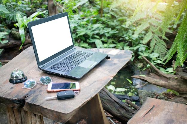 Komputerowy laptop z pustym bielu ekranem na drewnianym stole z zieleń ogródem