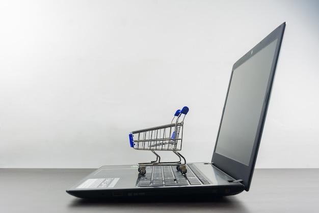 Komputerowy notatnik pusty ekran z wózek na zakupy na drewno stole