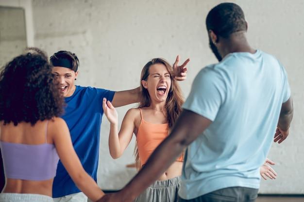 Komunikacja, emocje. grupa emocjonalnych młodych radosnych ludzi w zwykłych ubraniach, stojących blisko siebie w pomieszczeniu