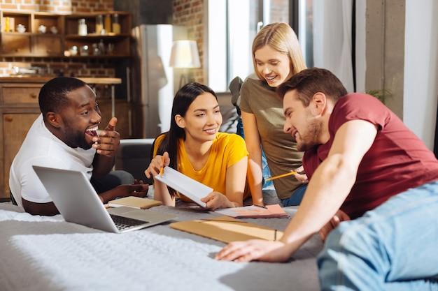 Komunikacja grupowa. czterech radosnych, wesołych, pozytywnych uczniów śmiejących się podczas plotkowania i omawiania planu