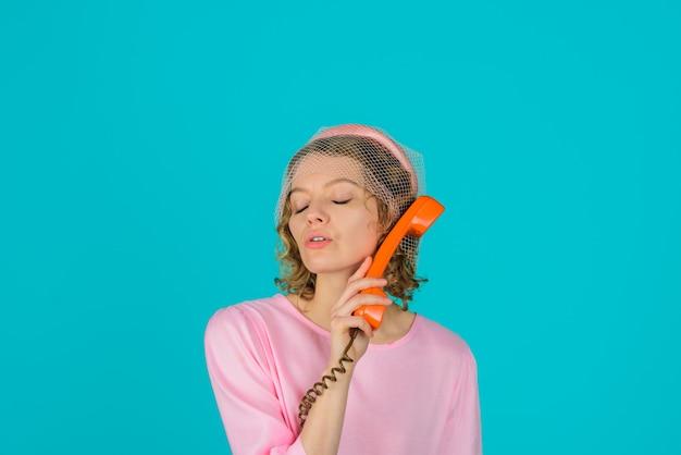 Komunikacja kobieta z retro telefonem urocza kobieta w różowej sukience ze słuchawką telefoniczną szczęśliwa kobieta
