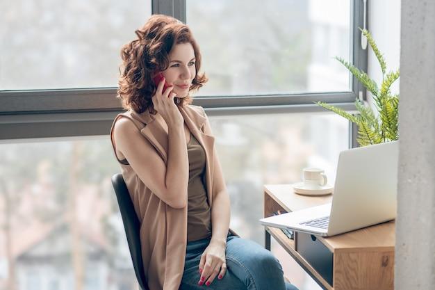 Komunikacja. młoda ładna kobieta rozmawia przez telefon i wygląda na zaangażowanego
