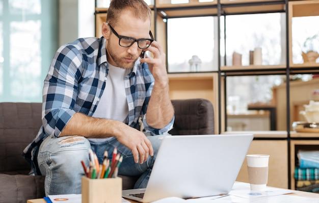 Komunikacja na odległość. poważny przystojny inteligentny mężczyzna siedzi przy laptopie i nawiązuje połączenie podczas pracy w biurze