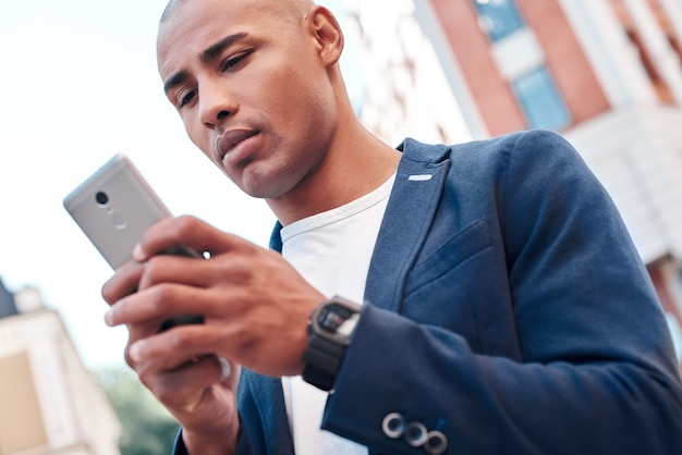 Komunikacja online młody mężczyzna stojący na ulicy miasta, trzymający smartfona rozmawiającego z przyjacielem