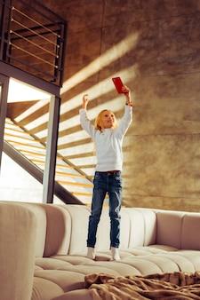 Komunikacja przez internet. urocza dziewczyna stojąca na kanapie i trzymająca smartfon w lewej ręce