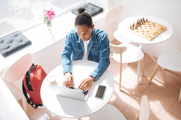 Komunikacja przez internet. uważna brunetka wpatrująca się w laptopa podczas pracy na odległość