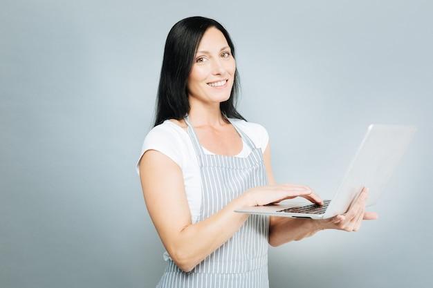 Komunikacja przez internet. zadowolona kobieta utrzymująca uśmiech na twarzy i trzymając laptopa, stojąc w półpozycji na szarym tle