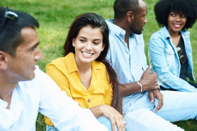 Komunikacja przyjaciół różnych ras na tle trawy w parku