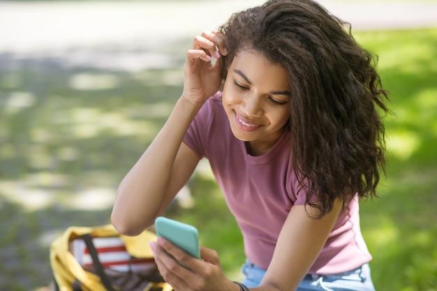 Komunikacja. urocza dziewczyna w różowej koszulce spędzająca czas w parku i rozmawiająca online