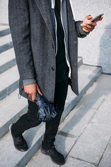 Komunikacja w mediach społecznościowych. moda w stylu ulicznym. nierozpoznawalny czarny mężczyzna na zewnątrz, deszczowa szara pogoda, nowoczesna technologia