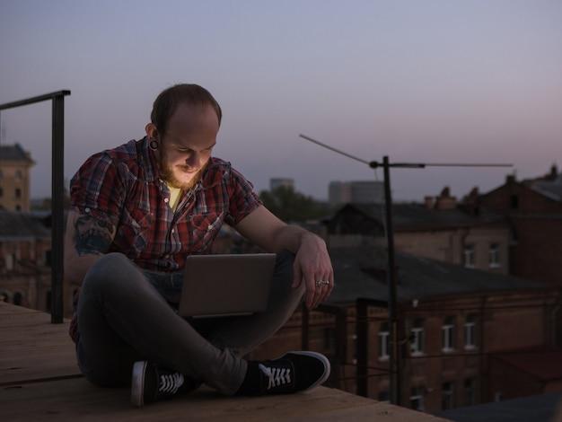 Komunikacja w mediach społecznościowych na zewnątrz. mężczyzna na dachu, szczęśliwy uśmiechnięty freelancer z laptopem w centrum uwagi na pierwszym planie, tło miejskie