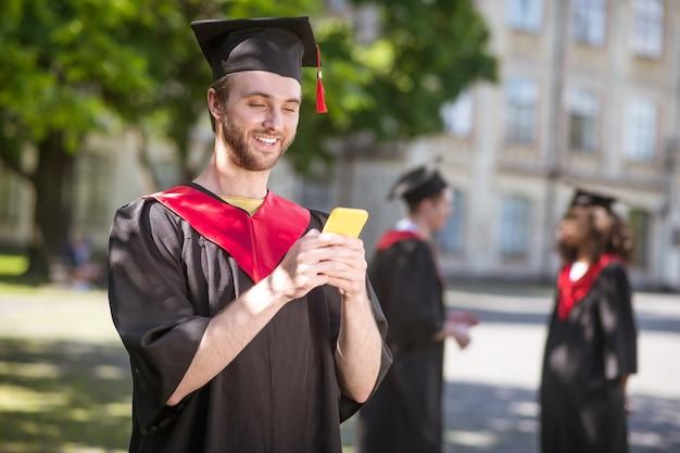 Komunikacja. wysoki, szczęśliwy absolwent wysyła sms-y i wygląda na podekscytowanego