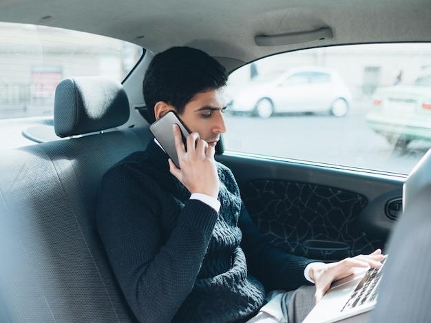 Komunikacja. zajęty program. napięty terminarz. biznesowy styl życia. mężczyzna rozmawia przez telefon i przegląda internet na laptopie na tylnym siedzeniu swojego samochodu