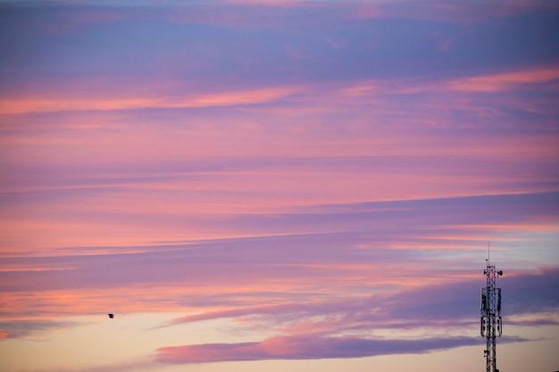 Komunikacyjny anteny wierza przy jutrzenkowym czasem z pięknymi kolorowymi chmurami przy nieba tłem