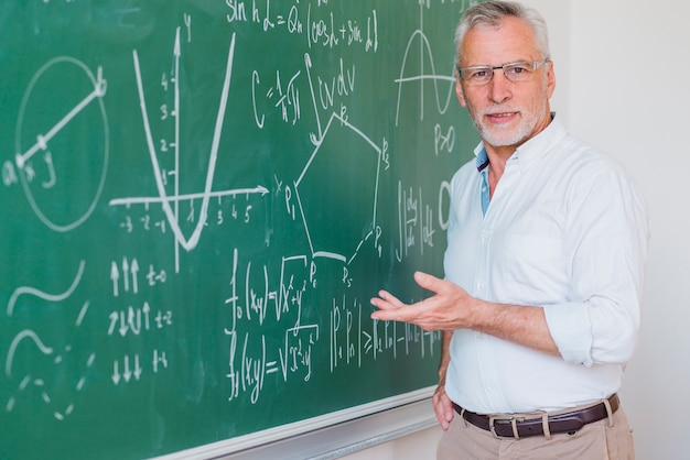 Komunikatywny męski wykładowca stoi przy blackboard i wskazuje przy równaniem