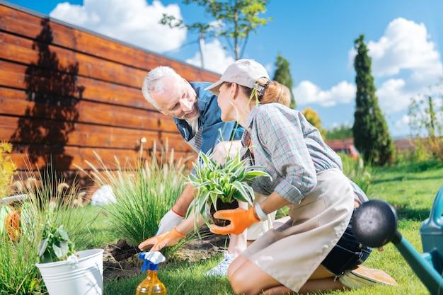Komunikowanie się z mężem. blondyneczka, kochająca, atrakcyjna żona rozmawia z mężem podczas sadzenia kwiatów