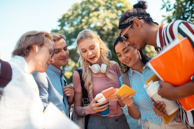 Komunikowanie się z przyjaciółmi. grupa uśmiechniętych uczniów stojących razem w kręgu i wysyłających sms-y do innych kolegów z grupy.